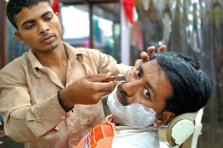 Man getting a shave with an open blade